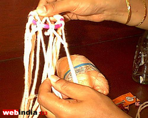 Nine triangular knots with nine pairs of wool thread hanging from it
